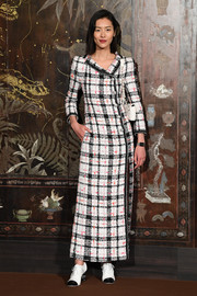 Liu Wen attended the Chanel Métiers d'Art show wearing a maxi blazer dress, in grid-patterned tweed.