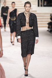 Gigi Hadid was sizzling on the Chanel Métiers d'Art runway wearing this black tweed skirt suit sans shirt.