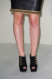 Leighton paired her leather dress with platform, peep toe ankle booties featuring gold hardware.