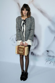 Alexa Chung sported a special edition tote bag from design house Chanel. It looks like it's from their recent spring 2010 line, where the running theme was little house on the prairie.