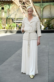 Tilda Swinton attended the Chanel Haute Couture show wearing a belted tweed jacket from the label.