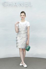 Mackenzie Foy attended the Chanel Couture Fall 2018 show wearing a tiered cocktail dress over a white tee.
