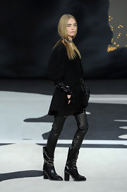 Cara Delevingne marched the Chanel runway wearing chained mid-calf leather boots.