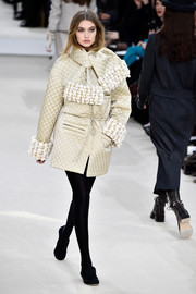 Gigi Hadid showed off a stylish quilted jacket with embellished cuffs and a matching scarf during the Chanel fashion show.