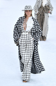 Cara Delevingne layered a houndstooth tweed coat over her jumpsuit. This was clashing patterns done right!