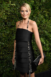 Margot Robbie paired a black satin clutch with a tiered halter dress for the Charles Finch and Chanel pre-Oscar dinner.