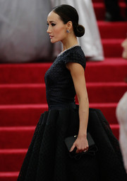 Maggie Q paired a bow-adorned satin clutch with a dramatic ball gown for the Met Gala.