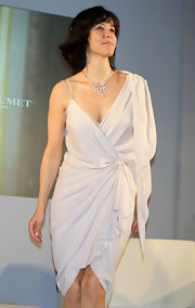 The French actress is a vision in this ivory draped one-shoulder dress.