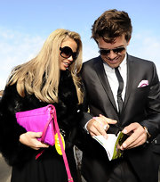 Katie Price added color to her monochromatic look with bright pink clutch.