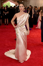Lizzy Caplan looked like a goddess at the Met Gala in a blush-colored Donna Karan Atelier one-shoulder gown featuring beads, fringes, and just a touch of Chinese influence.