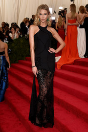 Karlie Kloss went for subdued sexiness at the Met Gala in a black Atelier Versace halter gown with a see-through skirt.