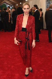 Sienna Miller complemented her red suit with a Rauwolf emerald-cut gemstone clutch.