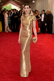 Anne Hathaway went for total shine with a metallic gold clutch by Benedetta Bruzziches.