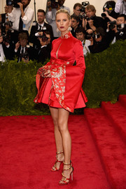 Karolina Kurkova put her mile-long legs on display at the Met Gala in a red Tommy Hilfiger mini dress with a Mandarin collar and super-flared sleeves.