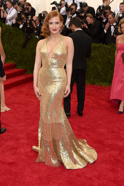 Jessica Chastain was a gilded bombshell in a figure-hugging sequined gold halter gown by Givenchy Couture during the Met Gala.