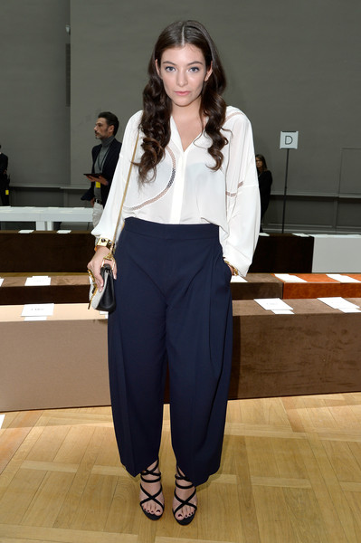 Lorde opted for a loose white mesh-trimmed button-down when she attended the Chloe fashion show.