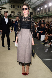 Ulyana Sergeenko attended the Chloe fashion show wearing a beige wraparound skirt over a black lace dress.