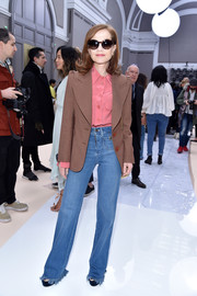 Isabelle Huppert sealed off her conservative look with a pair of flare jeans.