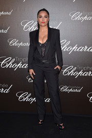 Salma Hayek was equal parts smart and sexy in a black Saint Laurent tuxedo jumpsuit layered over a lacy corset at the Chopard Trophy photocall.