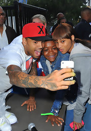Chris Brown was caught taking a quick selfie with kids while wearing a bright red baseball cap.