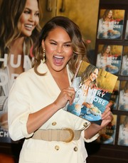 Chrissy Teigen attended her book signing wearing a cream blazer styled with a nude suede belt.