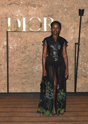 Lupita Nyong'o chose a shiny black wrap top by Dior for the brand's Cruise 2020 show.