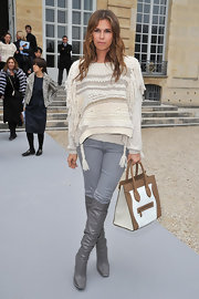 Dasha Zhukova kept her look effortless, layering a fringed sweater with sleek gray jeans.