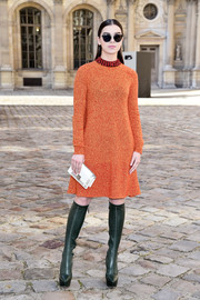 Hailee Steinfeld attended the Christian Dior fashion show looking retro-chic in an orange sweater dress from the label.
