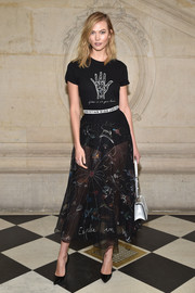 On the bottom half, Karlie Kloss went sexy in a sheer whimsical-print skirt, also by Dior.