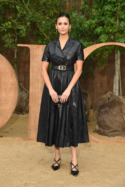 Nina Dobrev attended the Dior Spring 2020 show wearing a fitted black leather top from the brand.