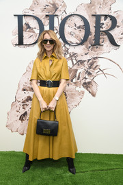 Celine Dion teamed her stylish frock with a black leather purse, also by Dior.