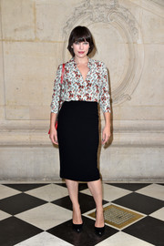 Milla Jovovich attended the Christian Dior fashion show wearing a printed button-down shirt.