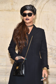 Rihanna attended the Dior fashion show carrying a black chain-strap leather bag from the label.