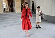 Giovanna Battaglia made a chic entrance in a red moto skirt suit at the Dior fashion show.
