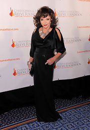 Joan proves she's still got it! She poses in a cut out blouse with a sparkling high waisted floor length skirt.