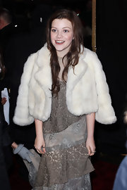 Georgie wears a thick cropped fur coat over her shoulders to keep warm at her premiere in London.