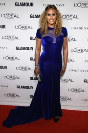 Laverne Cox owned the red carpet in a curve-hugging electric-blue gown by Marc Bouwer, featuring a sexy sheer panel and a long train, during the Glamour Women of the Year Awards.