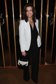 Gina Gershon topped off her black-and-white-themed ensemble with an embellished leather purse.