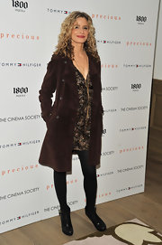 Kyra wore a textured, double-breasted evening coat over a printed cocktail dress with ankle boots.