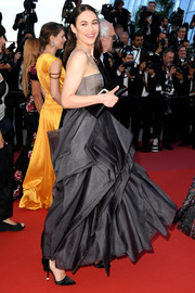 Olga Kurylenko walked the Cannes red carpet wearing elegant black satin pumps with ruffle detailing.