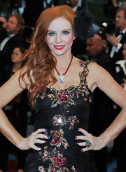 Phoebe Price wore her hair in long tousled waves and curls accented with a large feathered clip.