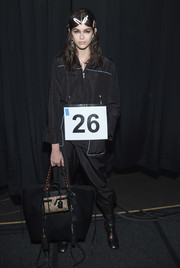 Kaia Gerber showed off a chic tasseled tote while posing backstage at the Coach fashion show.