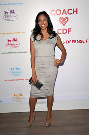 Rosario Dawson carried a glamorous silver python hard case clutch.