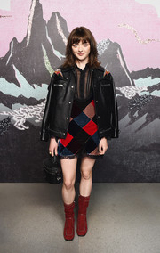 Maisie Williams rounded out her look with a pair of studded red suede boots.
