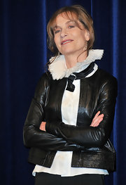 Isabelle Huppert layered a cropped black leather jacket over a blouse with a dramatic collar for a sophisticated finish.