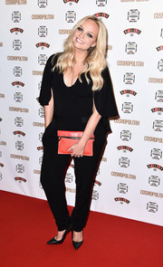 Emma Bunton accessorized with an orange leather clutch for a pop of color to her dark ensemble.