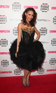 Amelle Berrabah donned a dramatic cocktail dress complete with a full tulle skirt. She topped off her look with glittering peep-toe pumps.