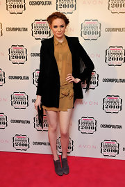 Karen wears a soft orange sheer button down dress under a black fringe jacket.