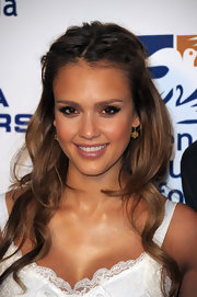 Jessica Alba styled her honey-brown hair in a half up hairstyle that was parted down the center and pinned on either side.