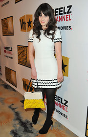 Zooey Deschanel added a burst of color to her black-and-white frock with a retro-style crochet frame clutch with yellow plastic beading.